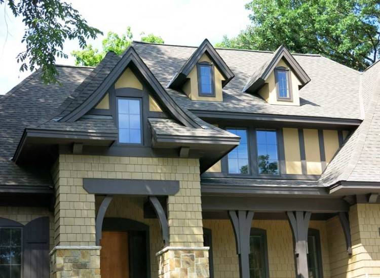 Tudor style home remodel with wood brackets, rain chain and muted exterior  trim details