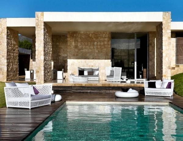 Mediterranean Style Home: The loggia is furnished as an outdoor living area,  complete with a raised cooking fireplace