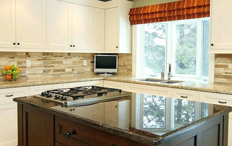 White kitchen cabinets, black countertops and white subway tile with white  grout