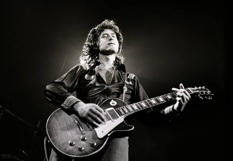 Jimmy Page performing live onstage, playing his Gibson Les Paul guitar
