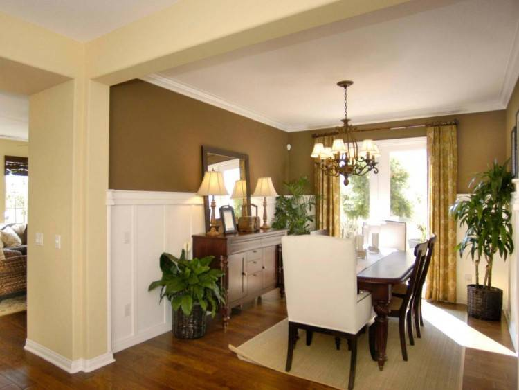 Chic dining room boasts upper walls clad in pale taupe grasscloth and lower  walls clad in wainscoting surrounding an oval pedestal dining table lined  with