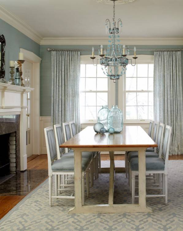 A white pleated chandelier illuminates a mahogany stained rectangular dining  table lined with seagrass dining chairs placed atop a denim blue striped rug