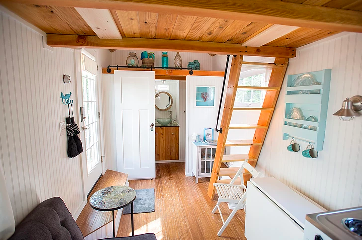Tiny house interior with white walls, white appliances, farmhouse sink,  wood bench, potted palm, lofted bed,wood floors, oriental rug, hanging  light,