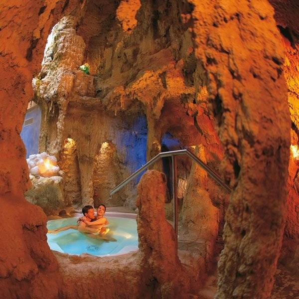 You can  construct a real or faux rock formation adjacent to the pool and include a pool  cave