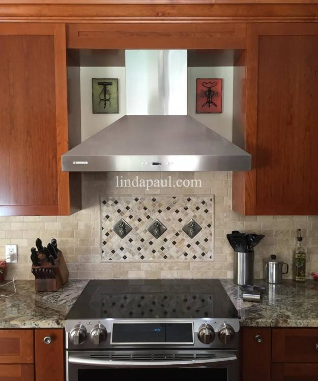 A light, aged brick backsplash with an inset center design with a chevron  pattern