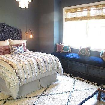 Bright, white bedroom with pretty Moroccan rug, indigo throw over white  linens, lots of pretty textiles